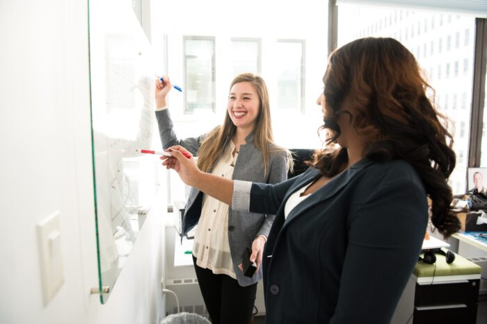 Two smartly dressed women writing on a whiteboard