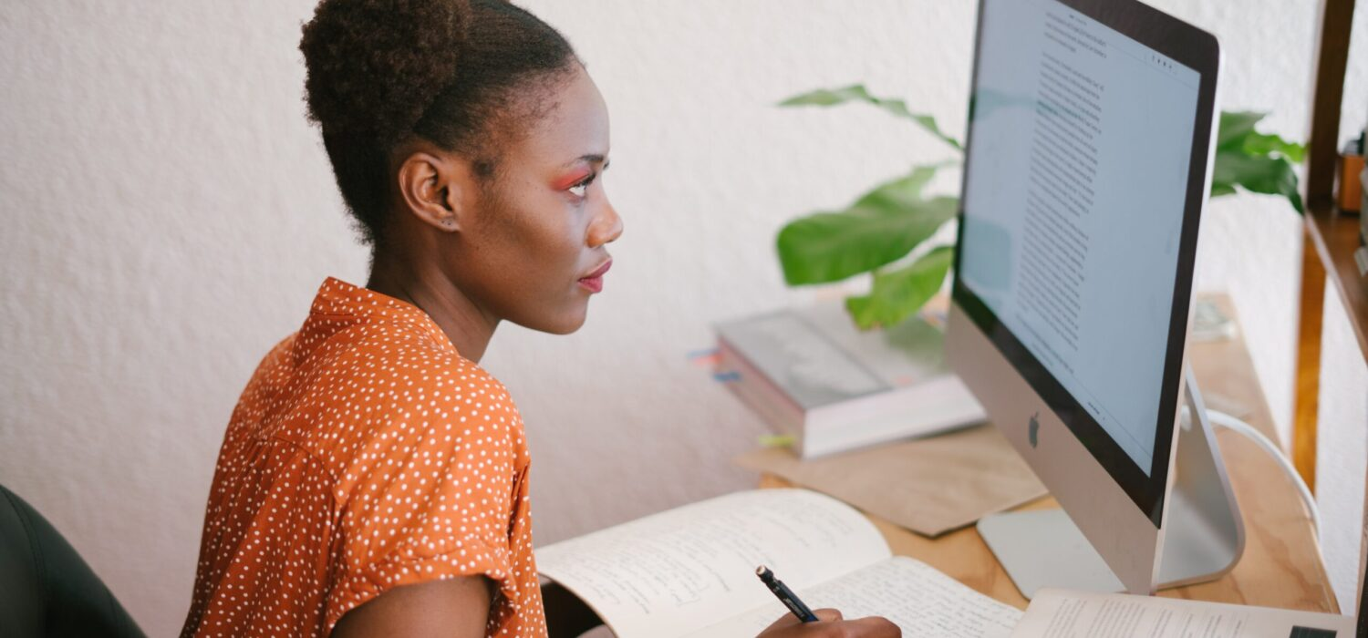 Woman studying looking at laptop making notes