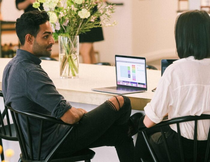 Man and woman collaborating on a studying project in front of a laptop