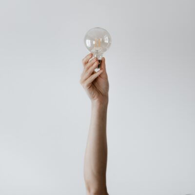 person holding a light bulb fully stretched